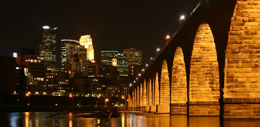 Stone arch bridge and Minneapolis skyline near vein treatment center in MN.