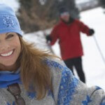 Woman cross country skiing in the snow with man behind her