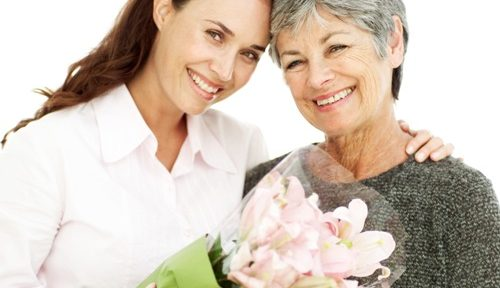 Adult mother giving her mother flowers on mother's day