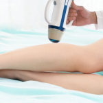 Minnesota Vein Center Specialist holding echotherapy wand over female patient leg